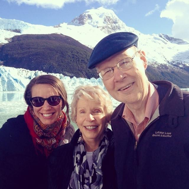 Jim, his wife Marianne, and their daughter smile in front of a snowy mountain peak.
